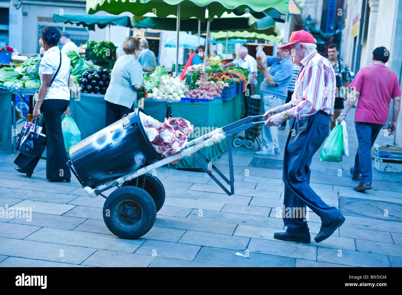 Old local man carrying meat in the market of La Boqueria in las Ramblas of Barcelona, Spain. - Stock Image