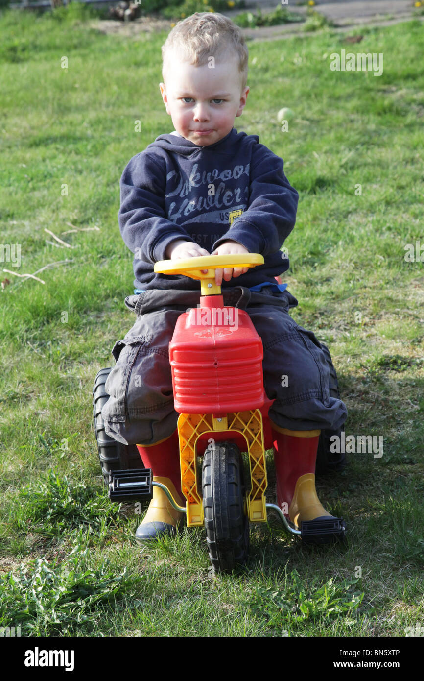 Toddler boy in the garden pretending to be a farmer driving a tractor and going beep! beep! MODEL RELEASED - Stock Image