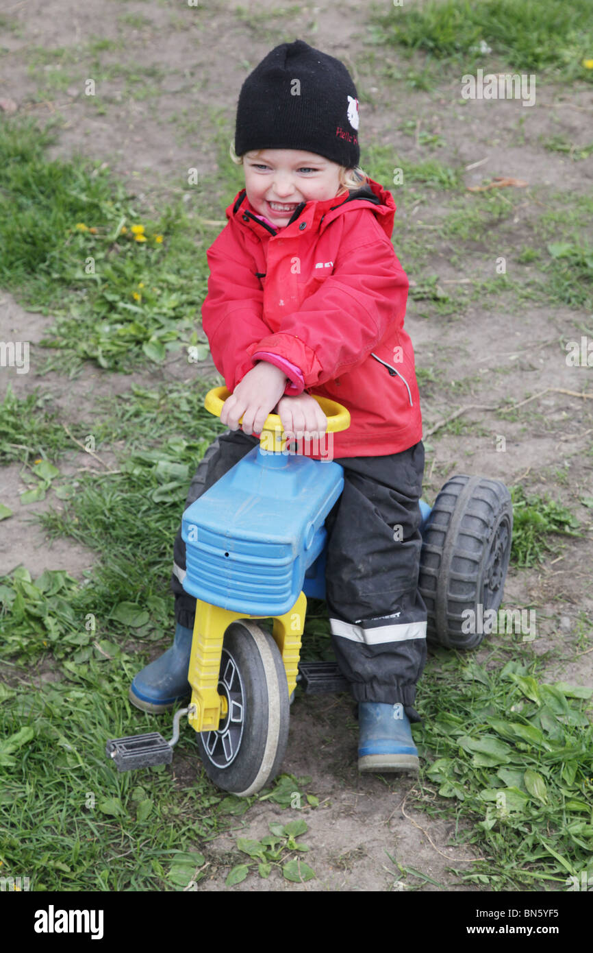 Toddler girl in nursery pretending to be a farmer with a tractor MODEL RELEASED - Stock Image