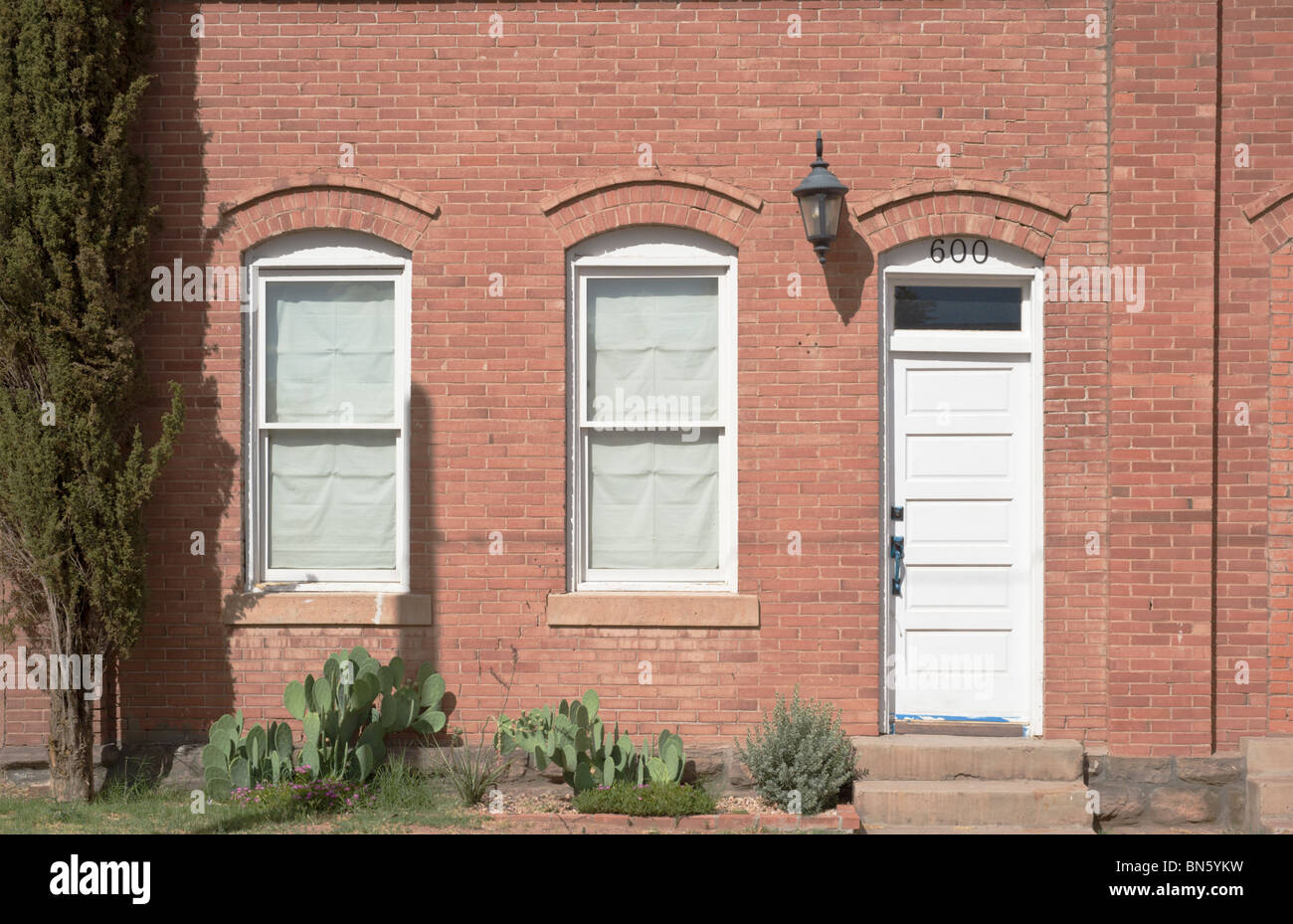 An old brick building with arched windows, and white door, is found in Tularosa, New Mexico. - Stock Image