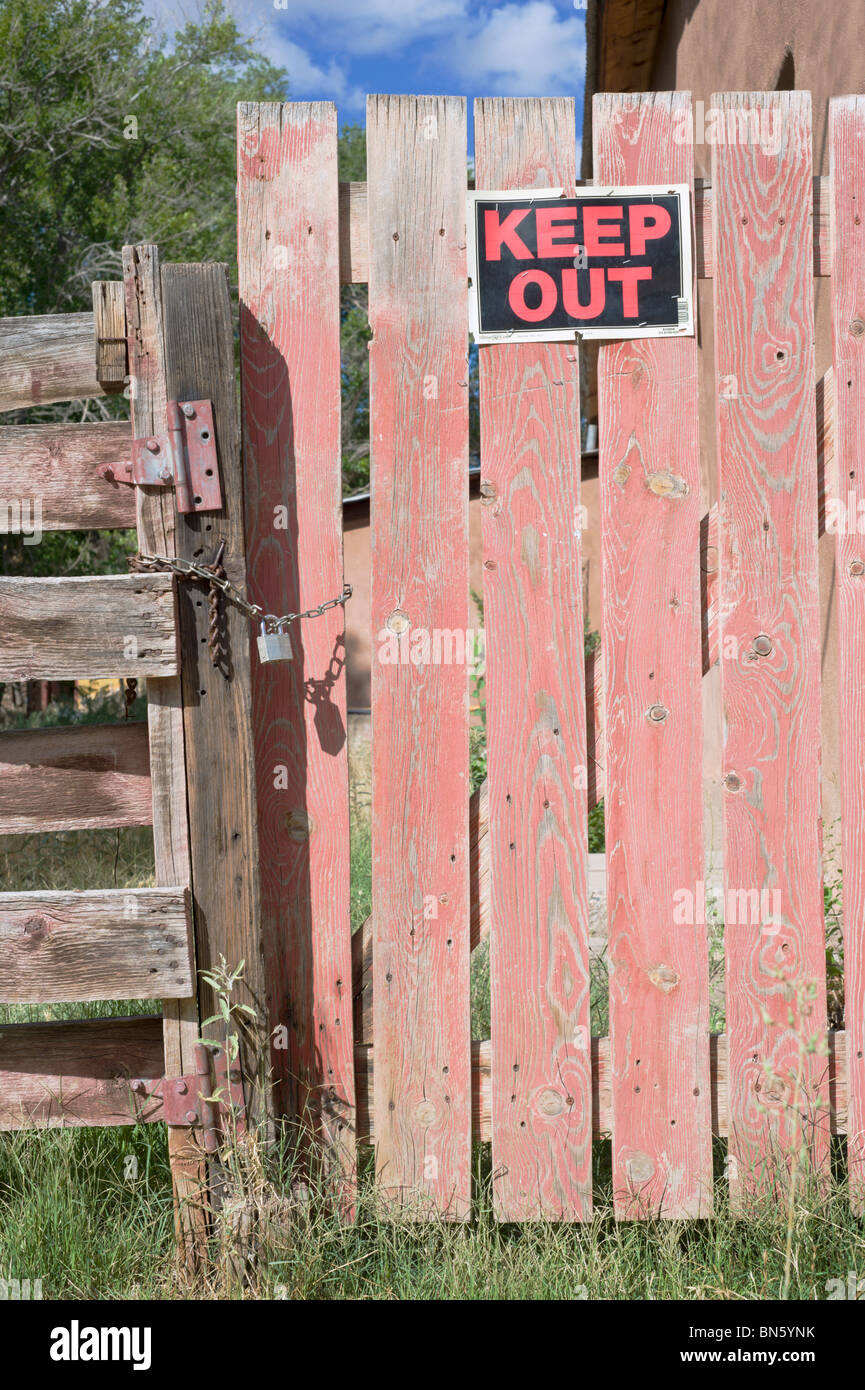 An old weathered wood fence and locked gate, with a 'KEEP OUT' sign posted, found on the side streets of - Stock Image