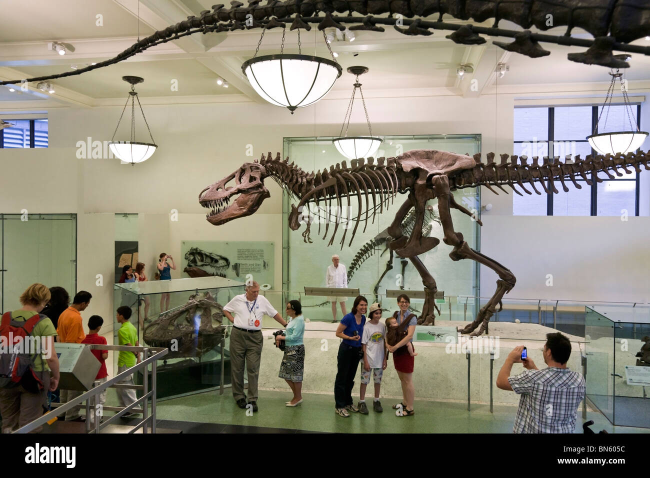 dad taking photo of happy family posing beside Tyrannosaurus Rex skeleton in American Museum of Natural History - Stock Image