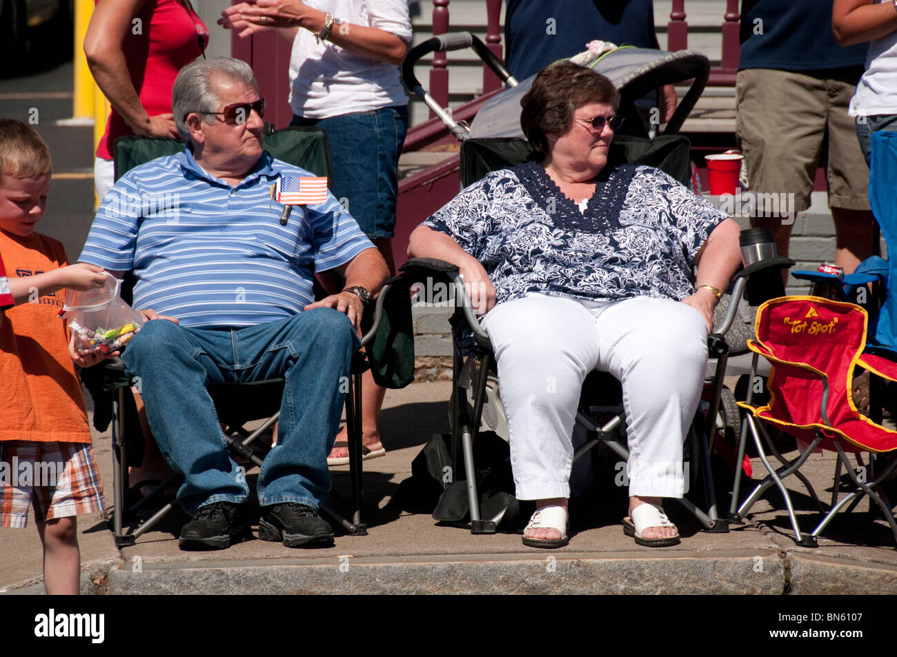 Overweight couple watching parade. - Stock Image
