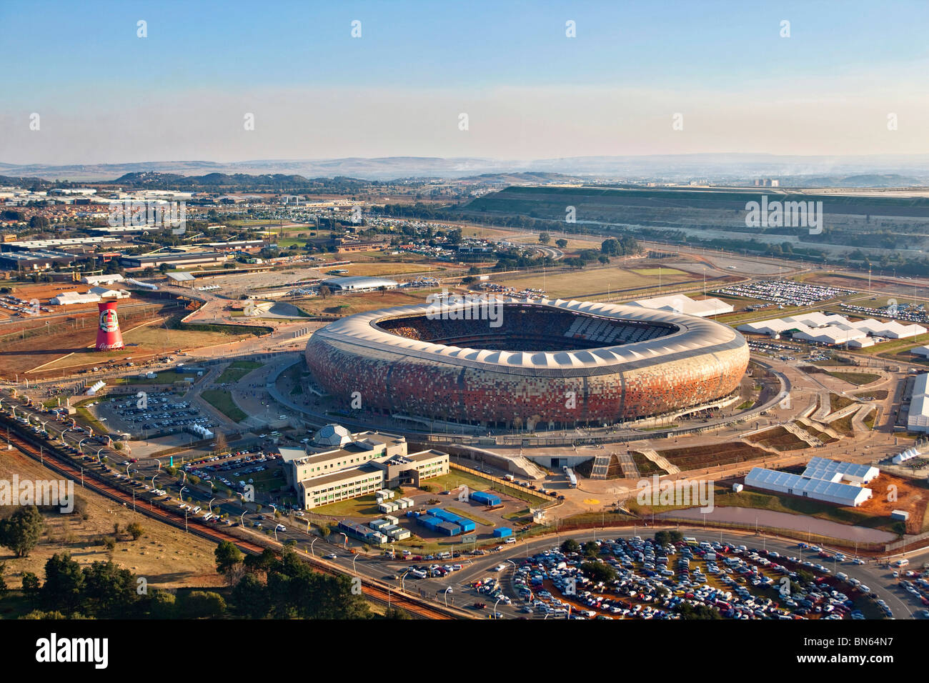 Aerial View of the FIFA 2010 Soccer City Stadium shaped like a calabash with the skyline of Johannesburg in the - Stock Image