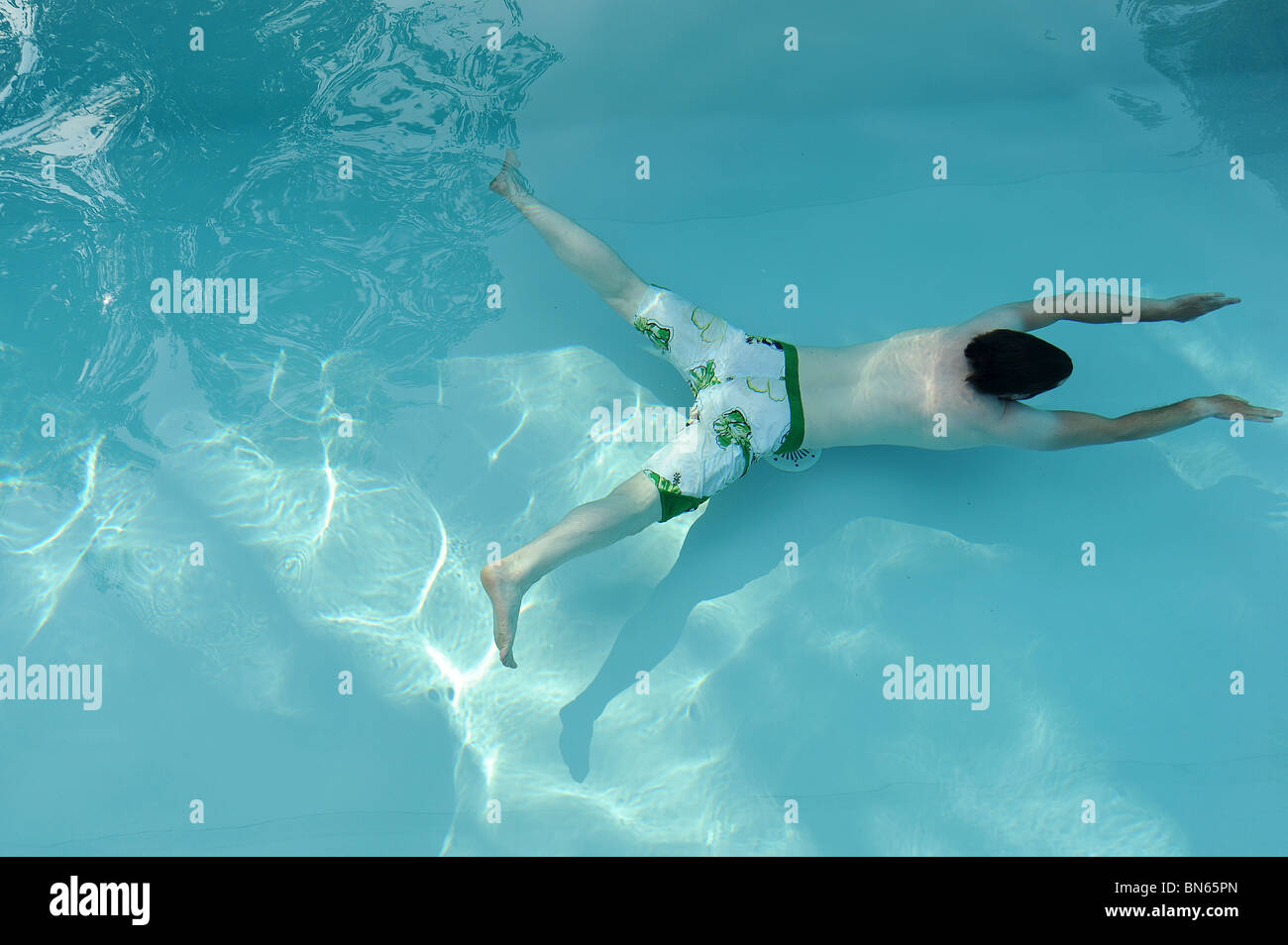 A man wearing board shorts swims under water in a swimming pool in Tours, France. - Stock Image