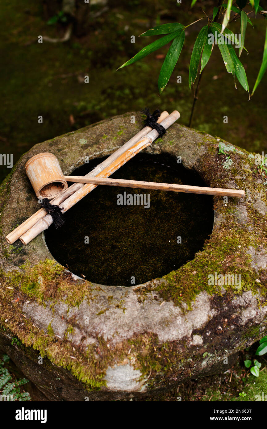 A stone basin with a bamboo dipper in the garden at Koto-in Temple. - Stock Image