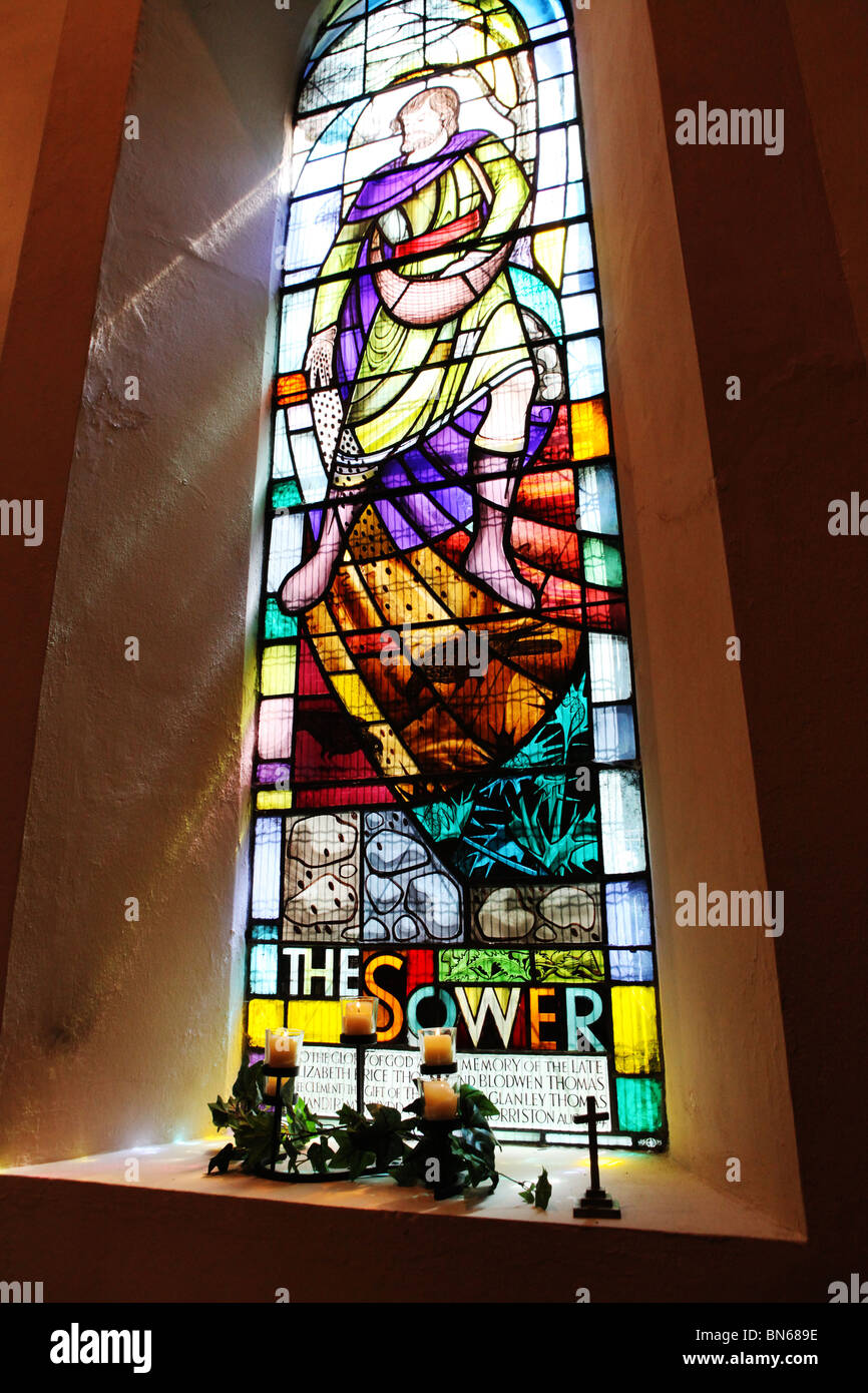 Sunlight shines through a beautiful colourful stained glass church window UK - Stock Image