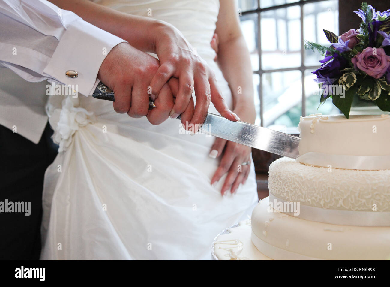 Bride and groom holding knife and cutting wedding white tiered cake bride and groom holding knife and cutting wedding white tiered cake on wedding day uk junglespirit Image collections