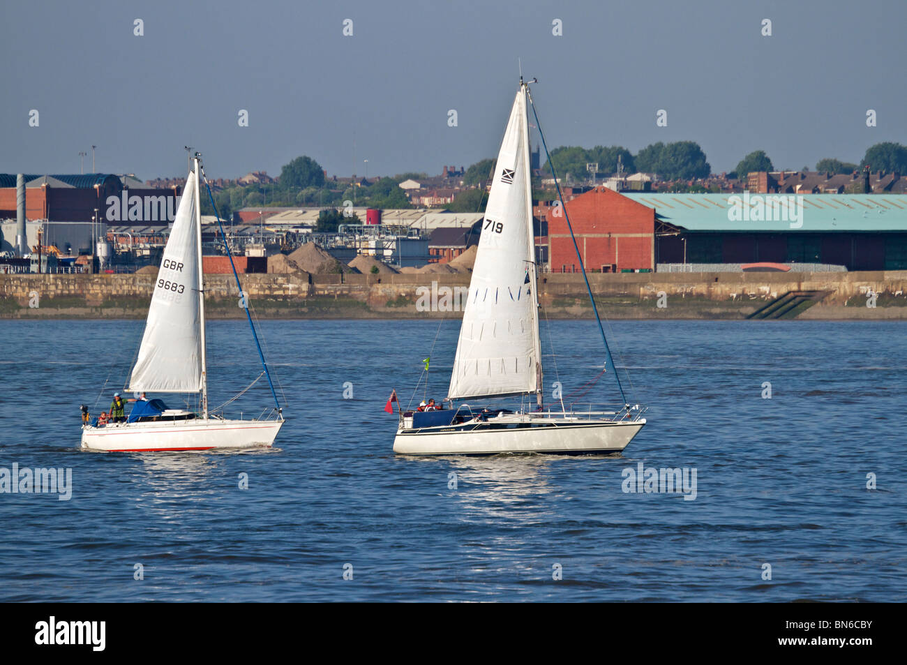 Two small sailing boats racing in river Mersey on a bright sunny evening. - Stock Image