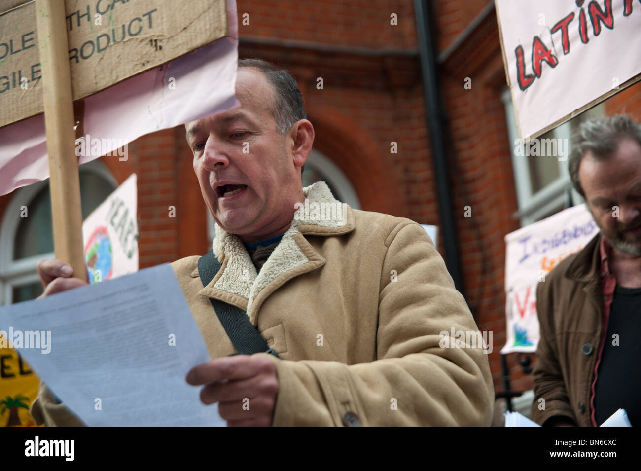 Mobilisation for Mother Earth protesters opposite the Colombian Embassy in London - man reads letter to be delivered - Stock Image