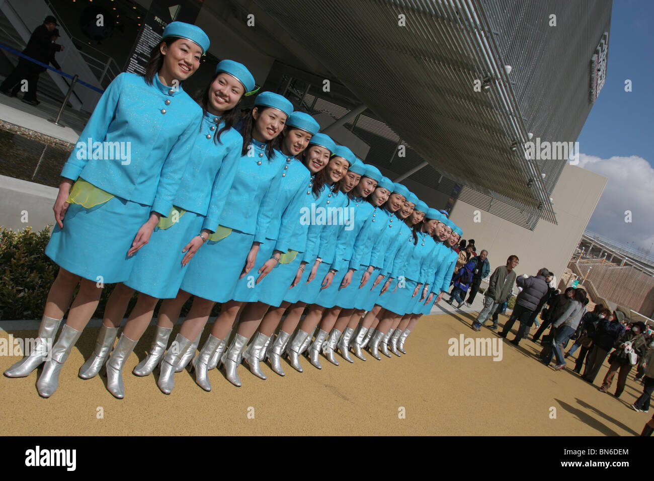 Japanese women wearing corporate uniforms greet visitors at the beginning of day, at World Expo 2005 in Aichi, Japan. - Stock Image