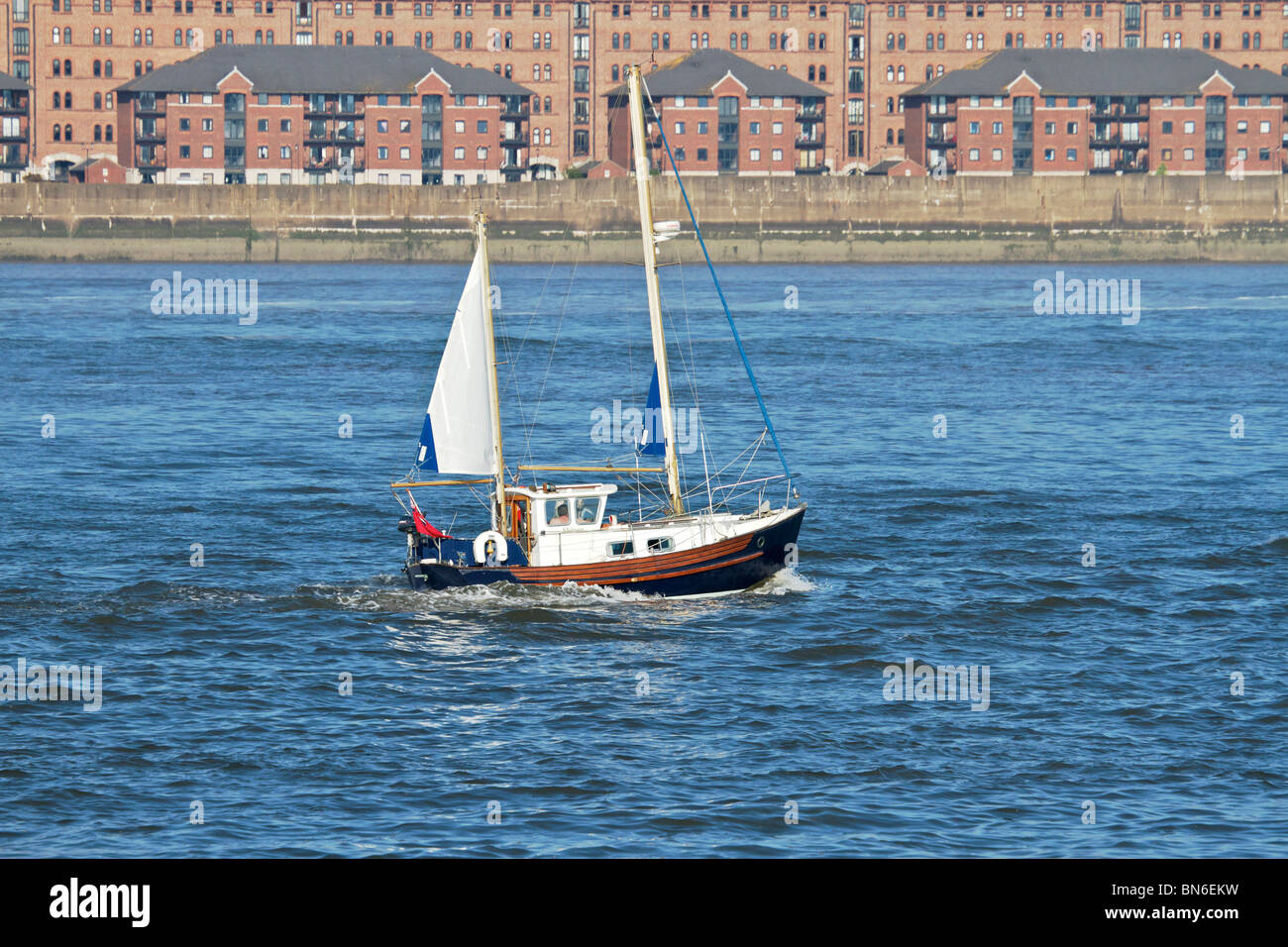 Small sailing boat heading up river Mersey on a bright sunny evening. - Stock Image