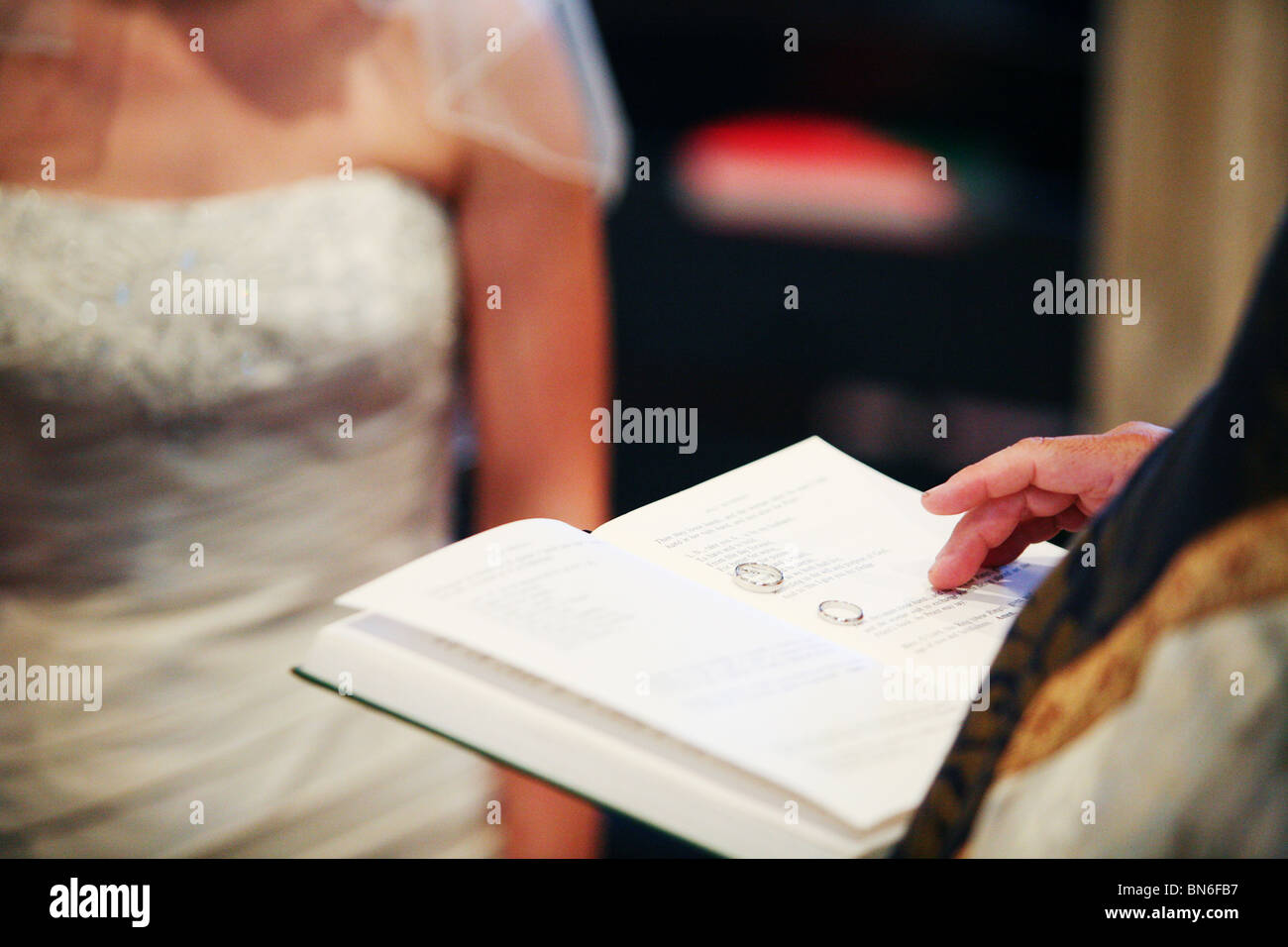 Wedding bands rings sitting on holy bible held by vicar priest during traditional religious church marriage ceremony Stock Photo