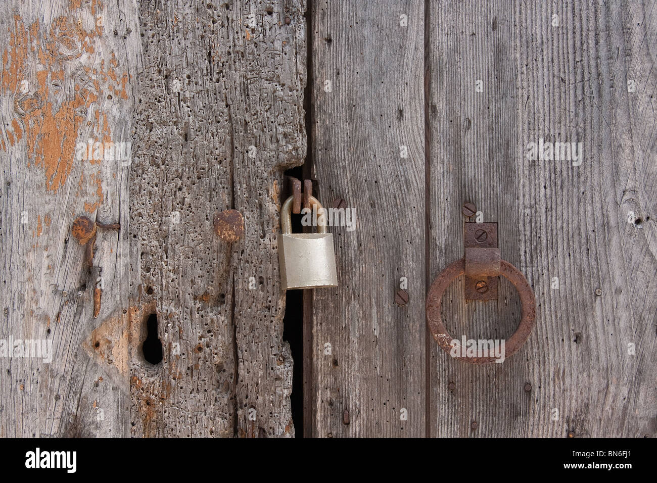 Old wooden planks door locked with rusty nails - Stock Image
