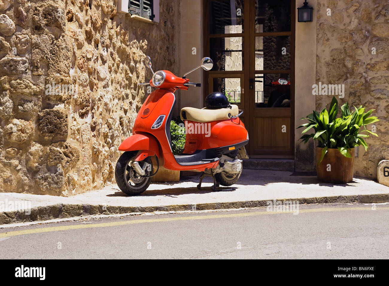 Red scooter parked in street. - Stock Image