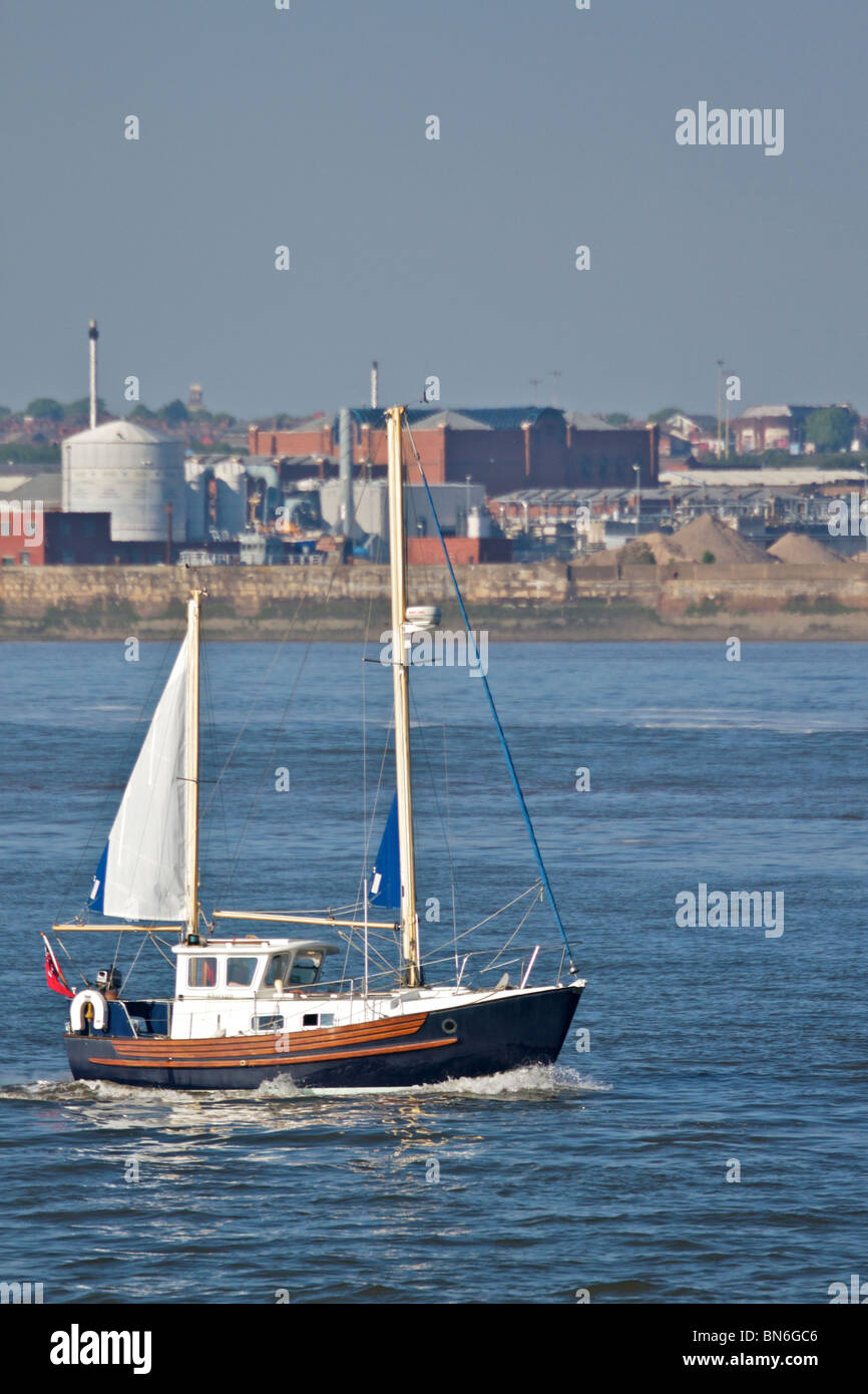 Small sailing boat heading up river Mersey on a bright sunny evening. Merseyside, England UK May 2010 - Stock Image