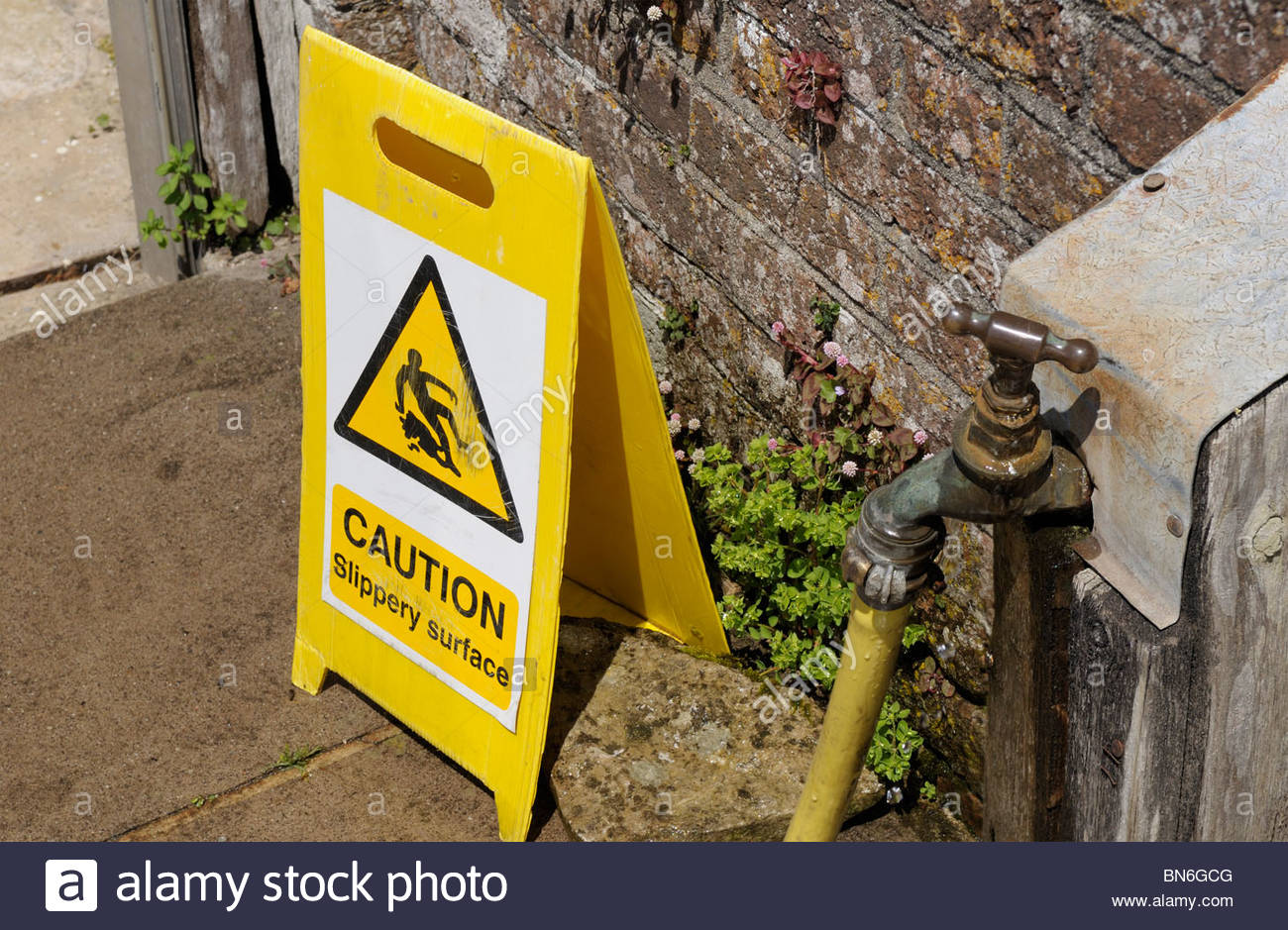Top down image of a Caution - Slippery Surface warning sign, England, UK - Stock Image