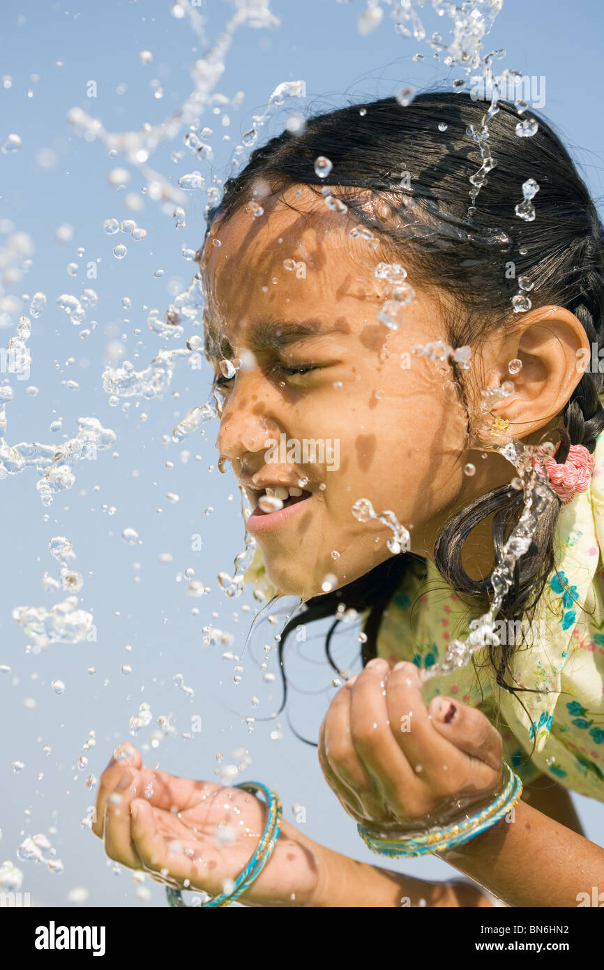 Indian girl splashing water on himself against a blue sky. India - Stock Image