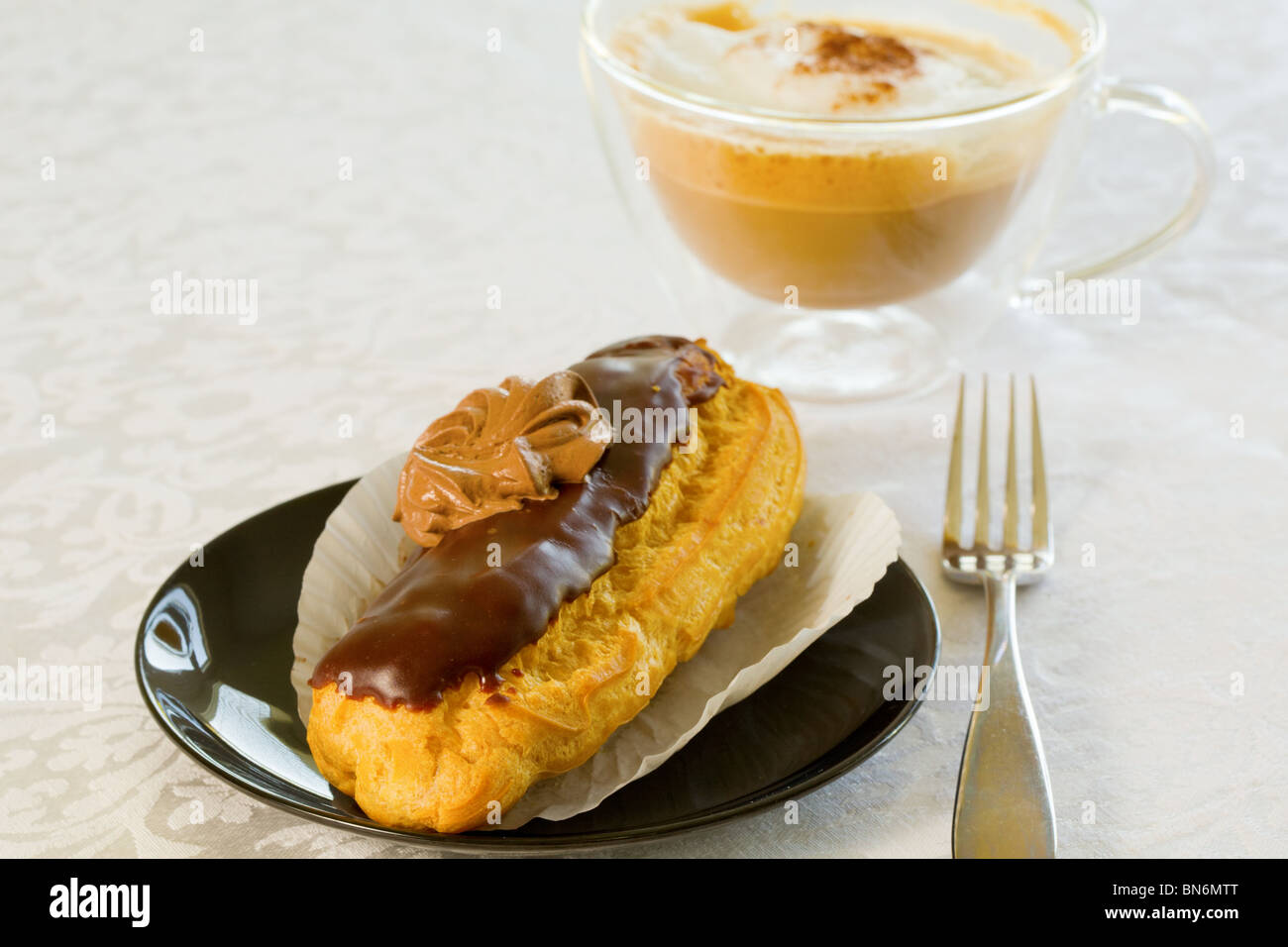 Eclair with a cup of cappuccino - Stock Image