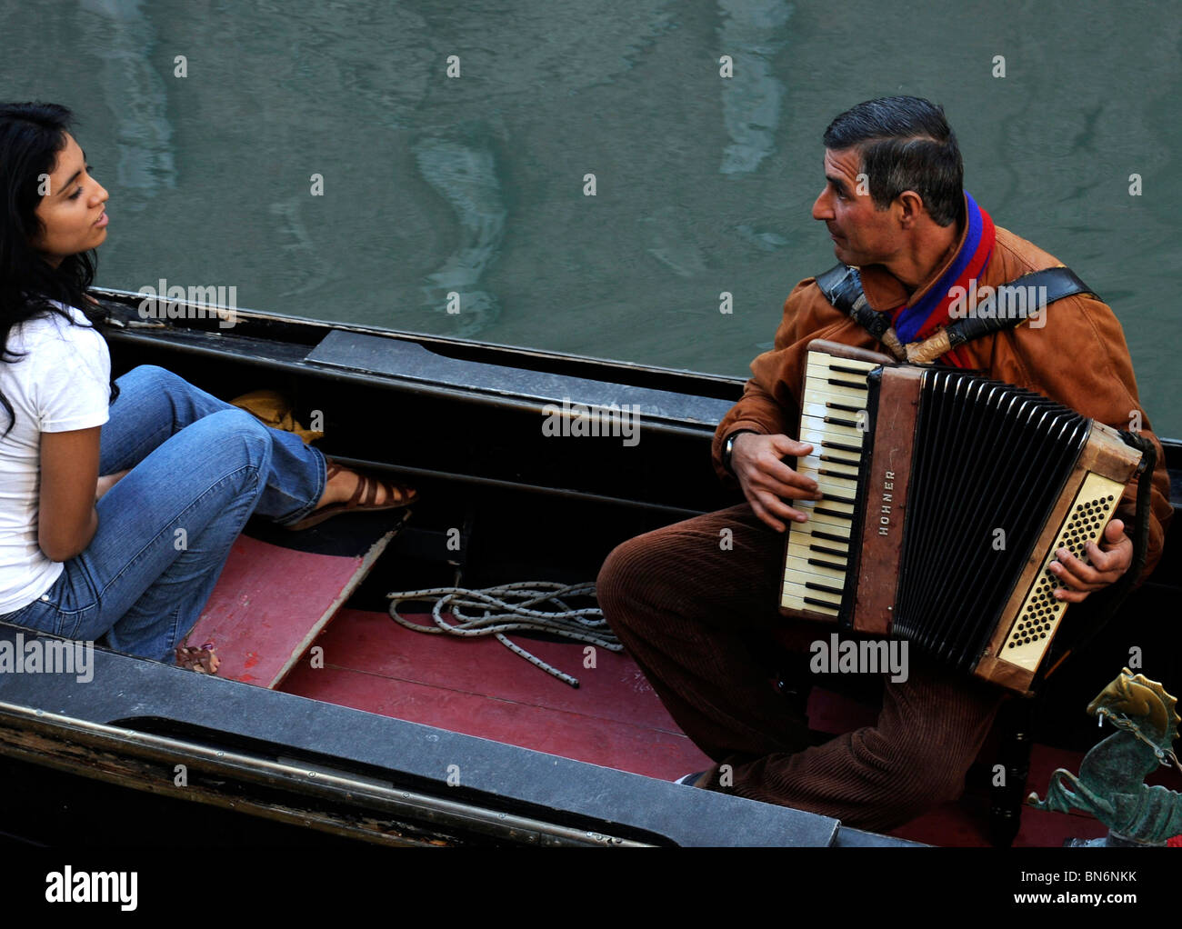 Accordianist serenades young girl on gondola in Venice Italy - Stock Image