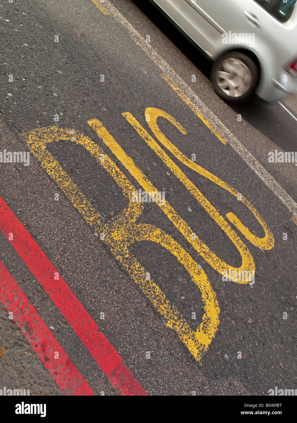 Bus lane and red route lines painted on a road in North London England UK designed to keep traffic moving - Stock Image