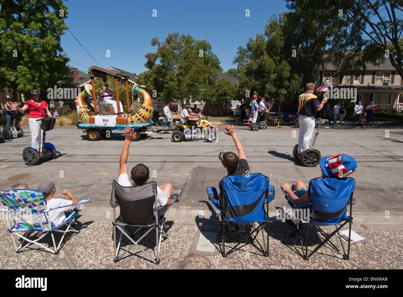 Spectators wave to Steve Wozniak as he and his posse on Segways pass during a 4th of July Parade in San Jose, CA. - Stock Image