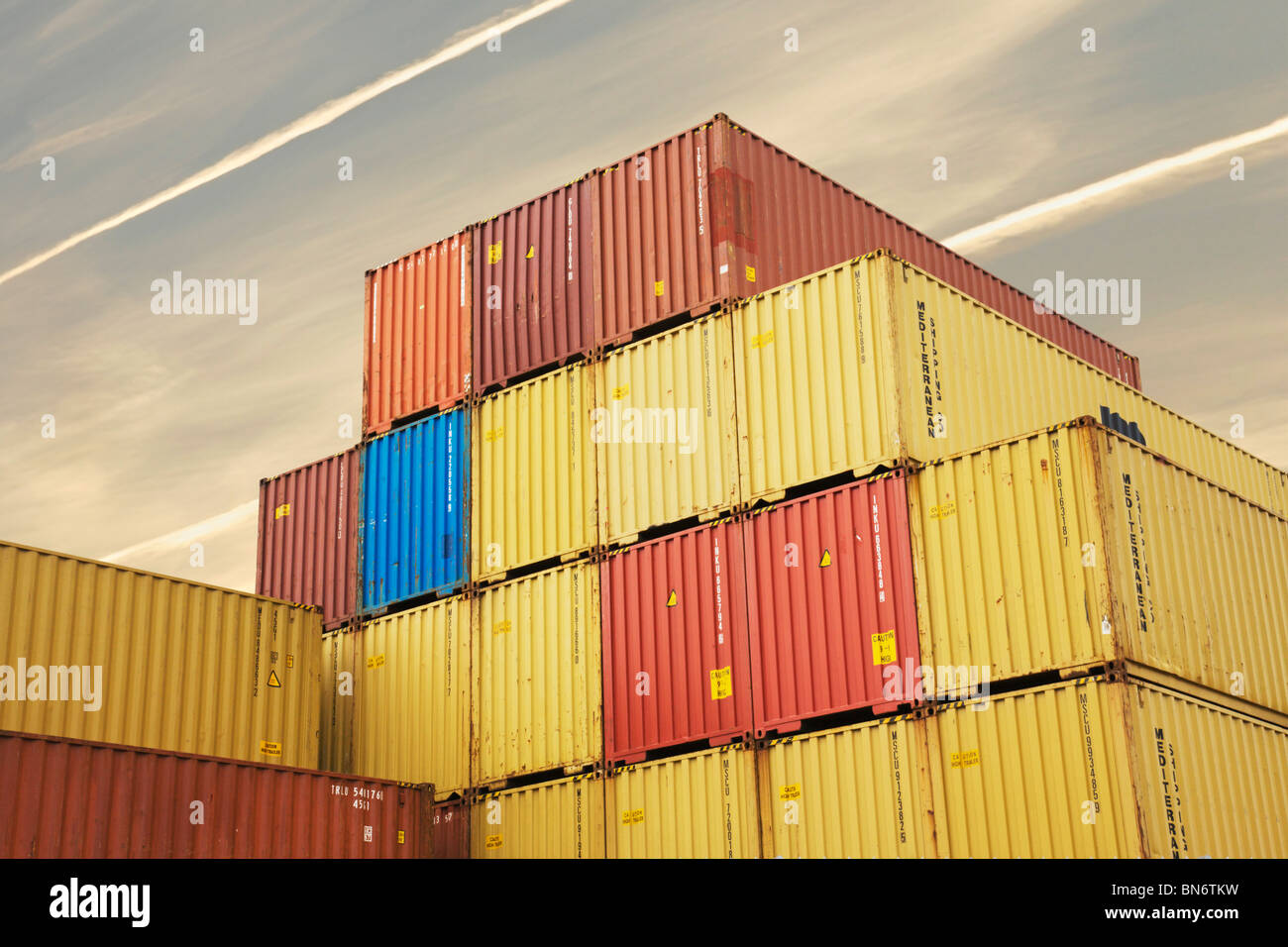 Shipping containers under jet trails. - Stock Image