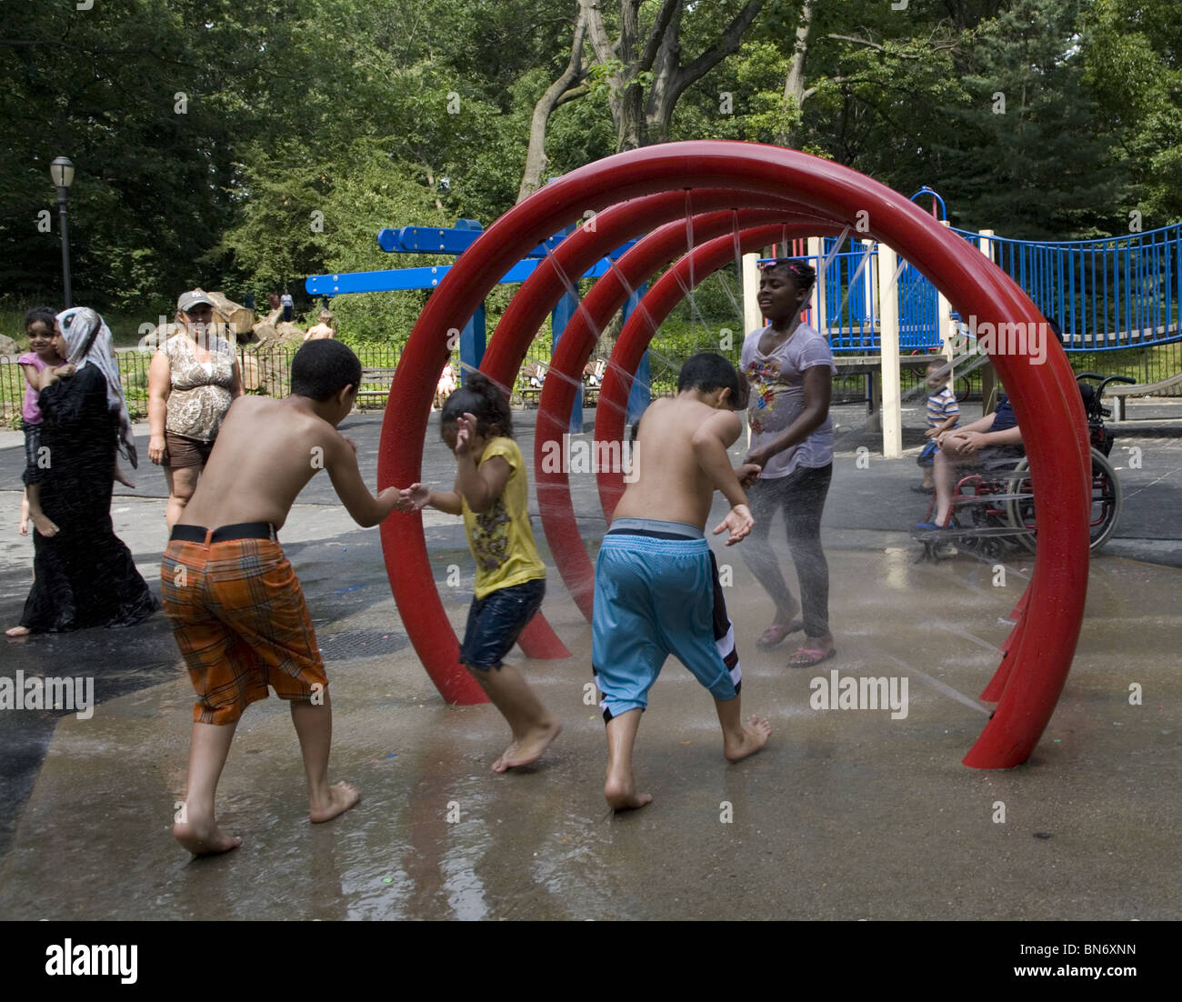 Children cool off in the water area on a hot summer day at the 3rd St. playground in Prospect Park, Brooklyn, NY. - Stock Image