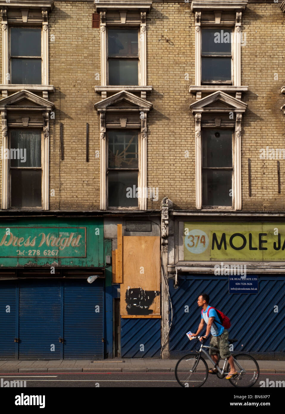 Run down and boarded up shops and offices in King's Cross north London England UK showing inner city urban decay - Stock Image