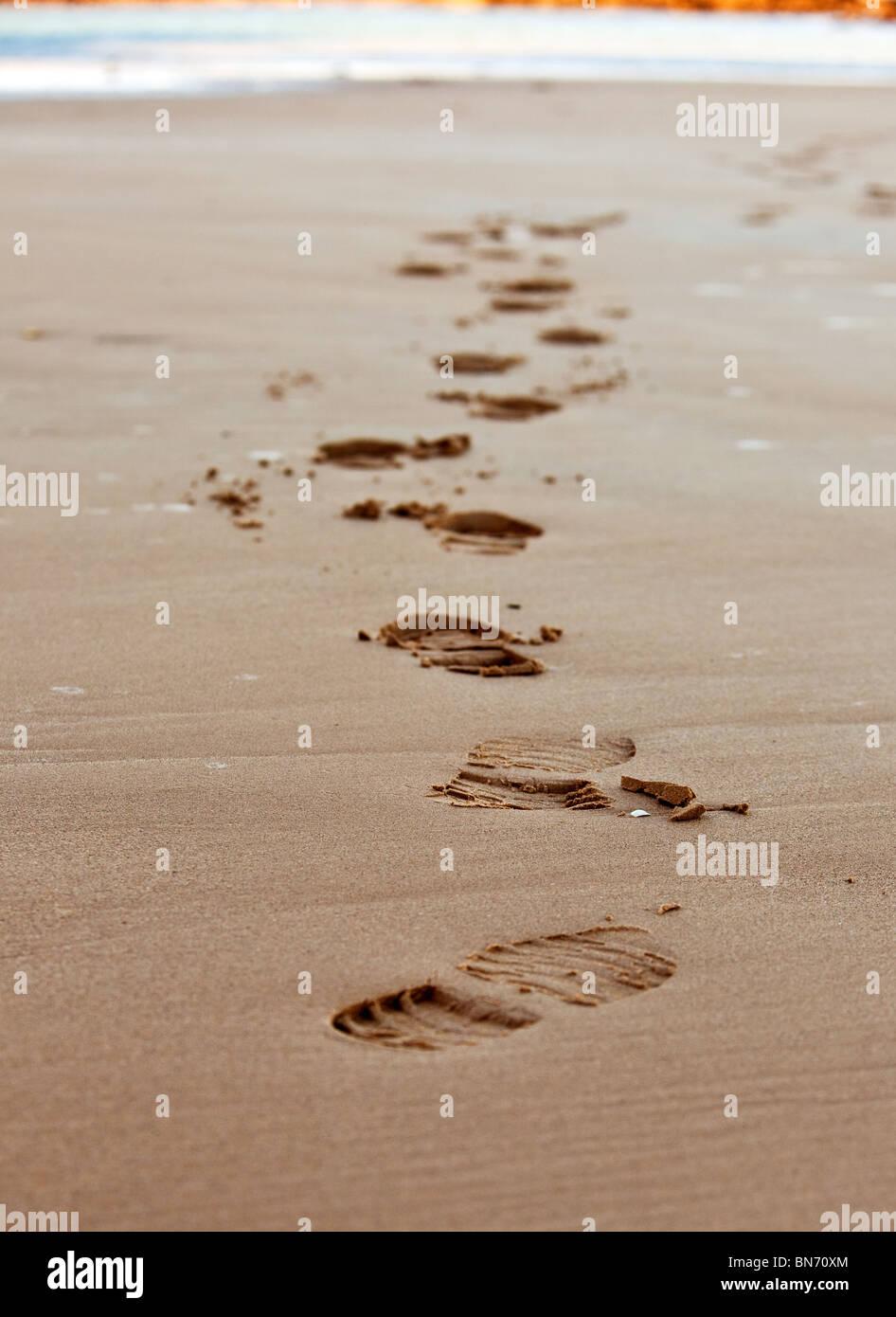 footprints chain on sand of sea coastline. small GRIP - Stock Image