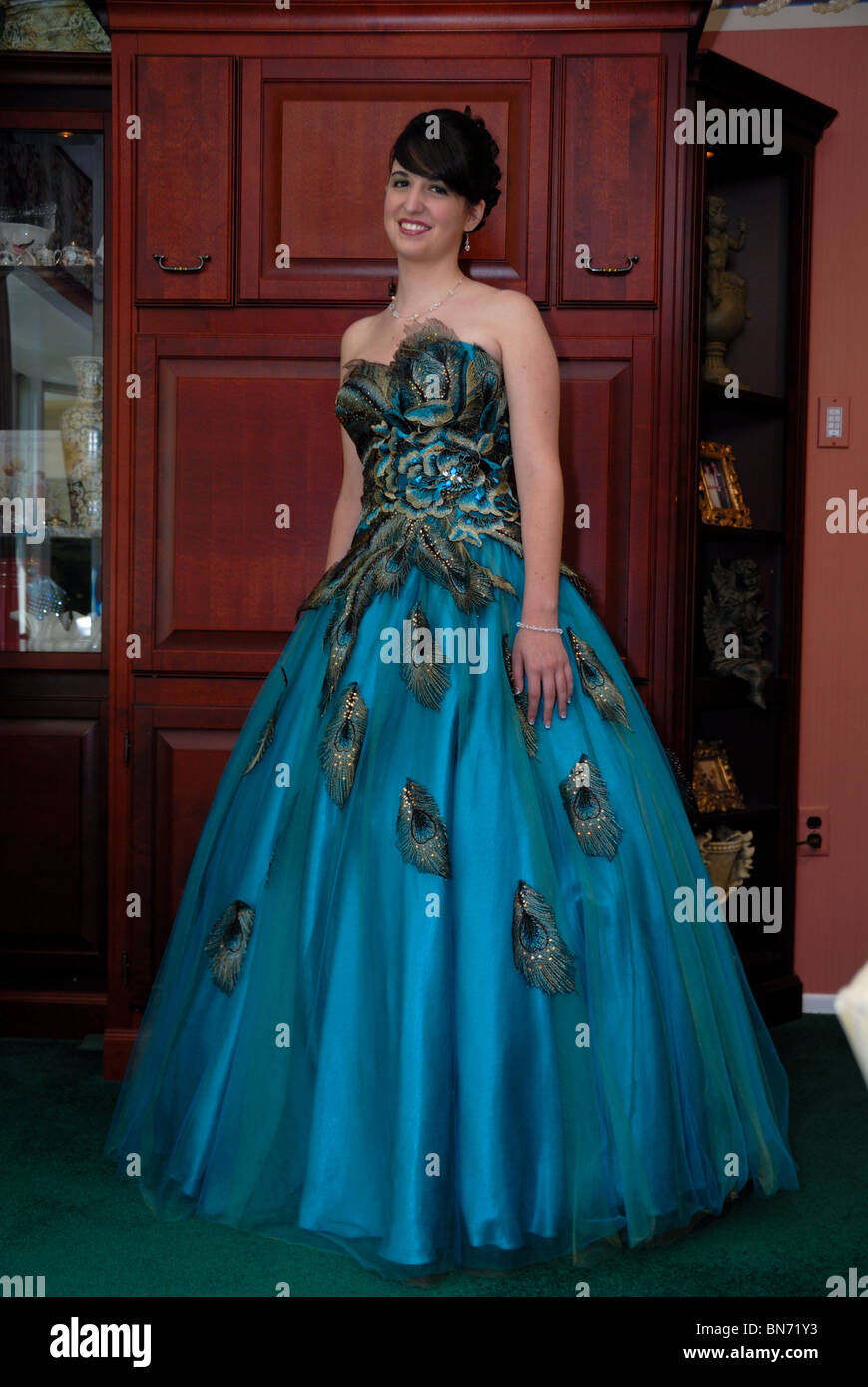 A teenager in a beautiful aqua colored prom dress in an elegant ...