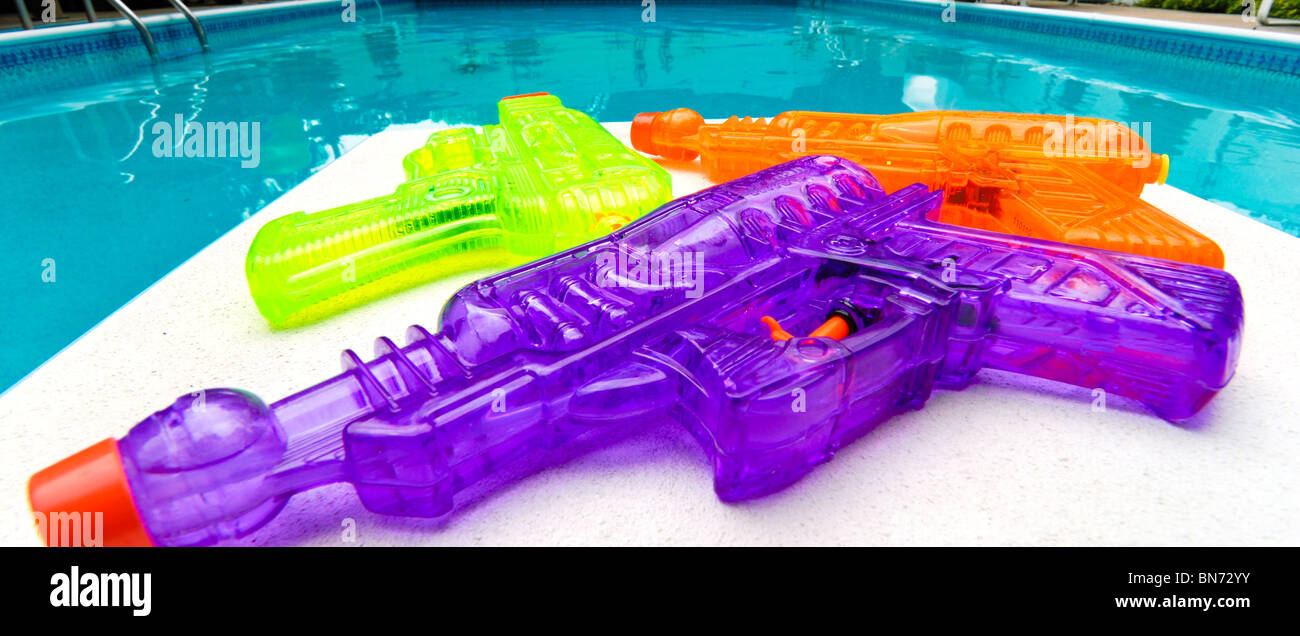 Purple, green and orange neon colored squirt guns are ready for some poolside action. - Stock Image