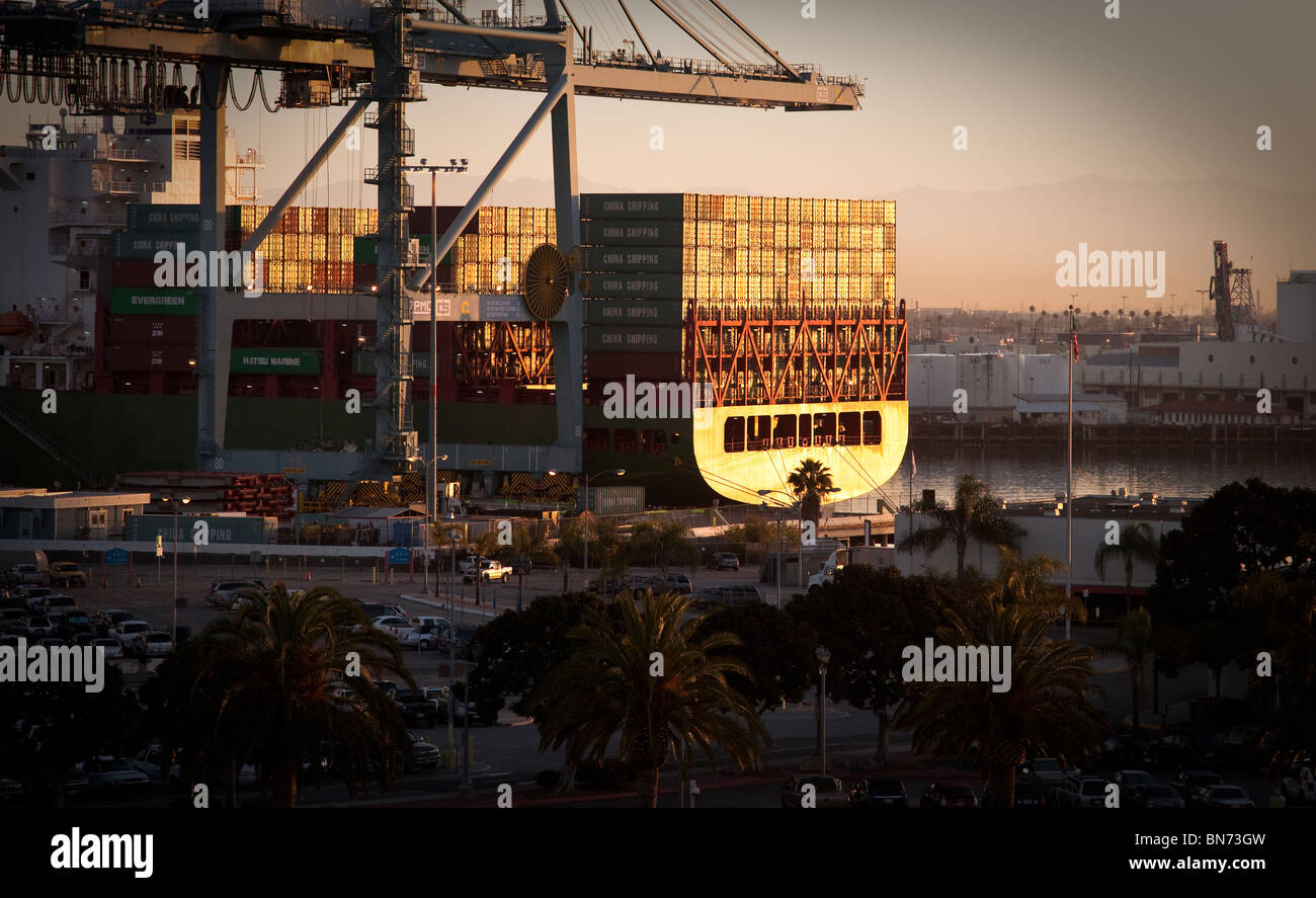 Port of Long Beach, Los Angeles, California at sunrise. Barge heavily loaded with Shipping Containers in morning Stock Photo