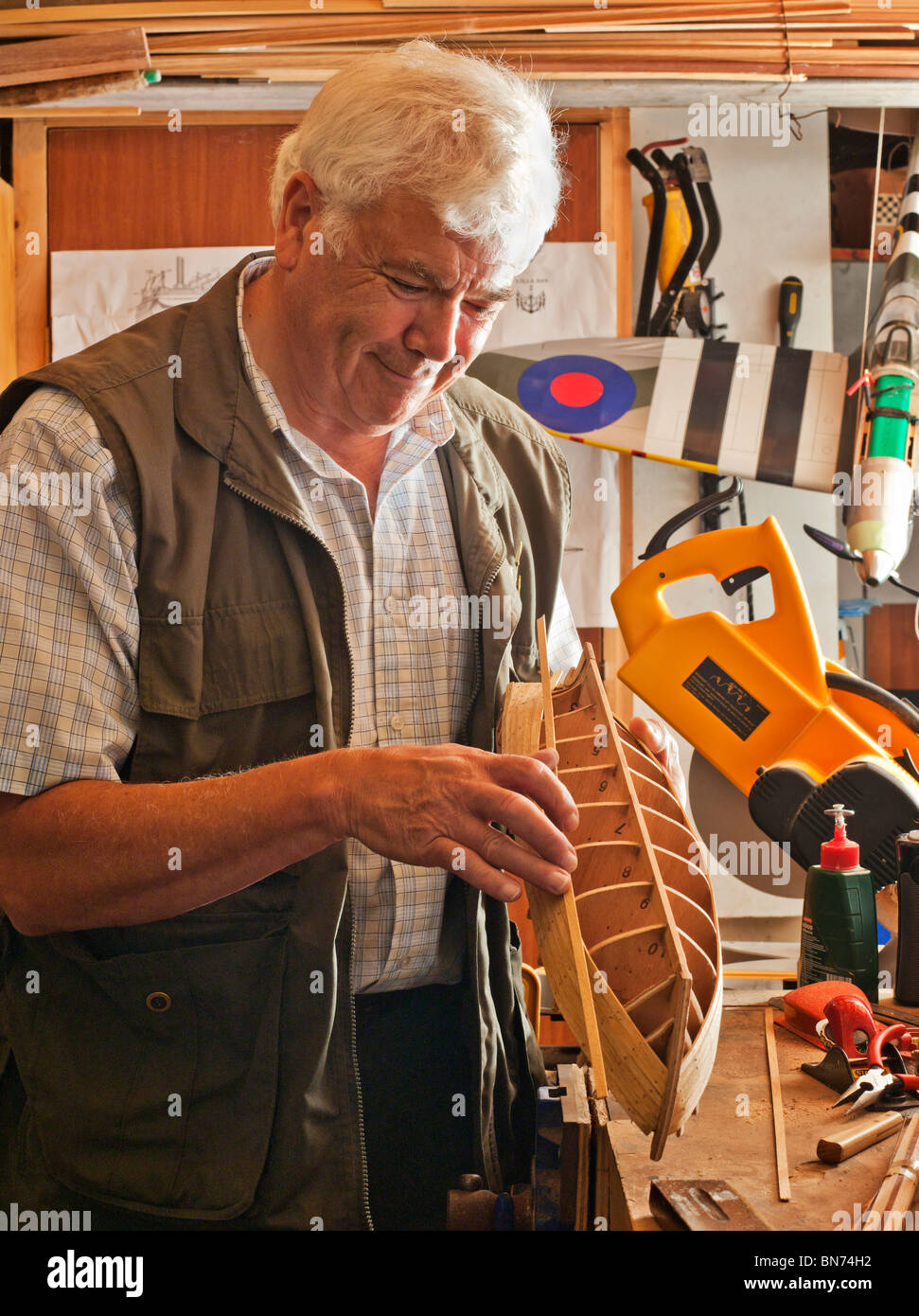 Retired man making wooden model boat. - Stock Image