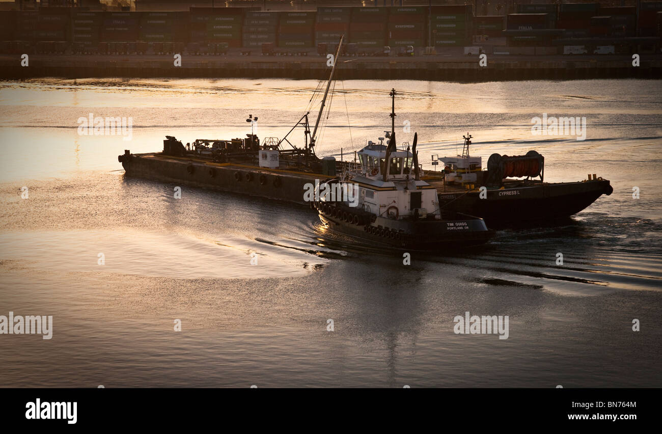 Port of Long Beach, Los Angeles, California at sunrise. A Tug boat is pushing a barge in early morning light. - Stock Image