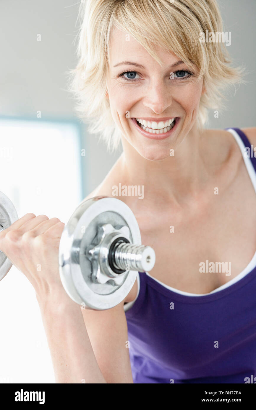 Woman with dumbbell smiling to camera - Stock Image