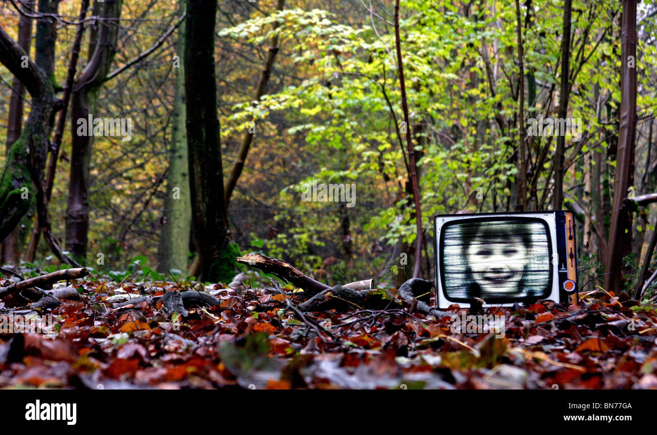 old television found in a wood with a boy's face superimposed - Stock Image