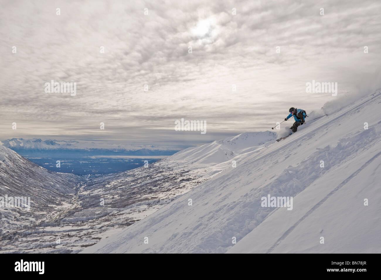 A woman backcountry skier enjoys some powdery turns in Hatcher Pass, Alaska - Stock Image