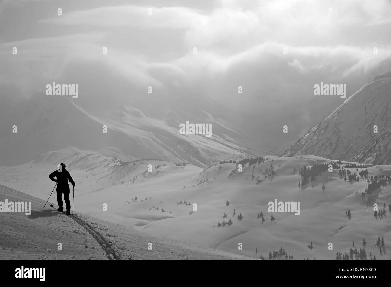 A backcountry skier stands on a ridge in Turnagain Pass, Alaska - Stock Image