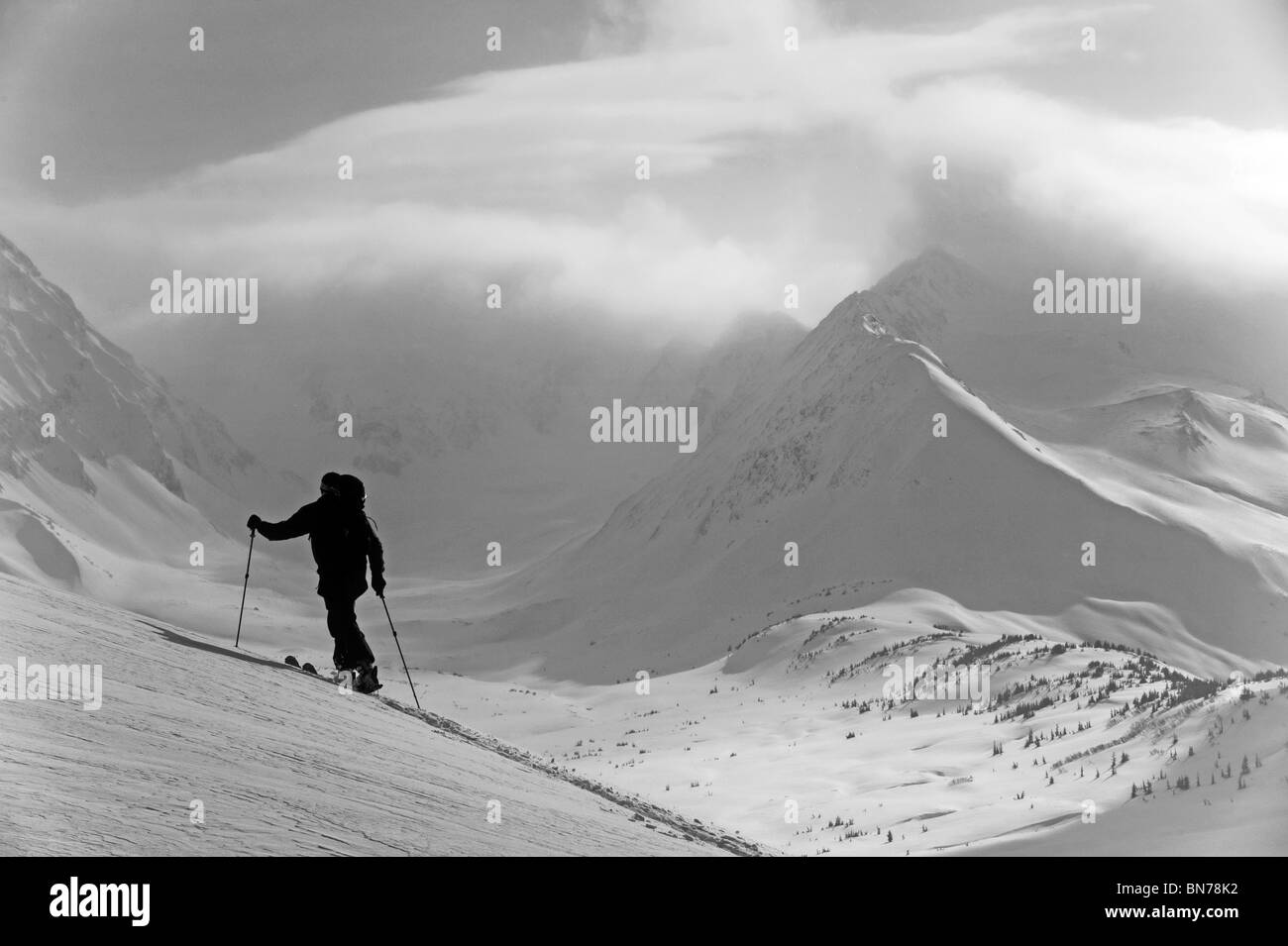 A backcountry skier skinning uphill in Turnagain Pass, Alaska - Stock Image