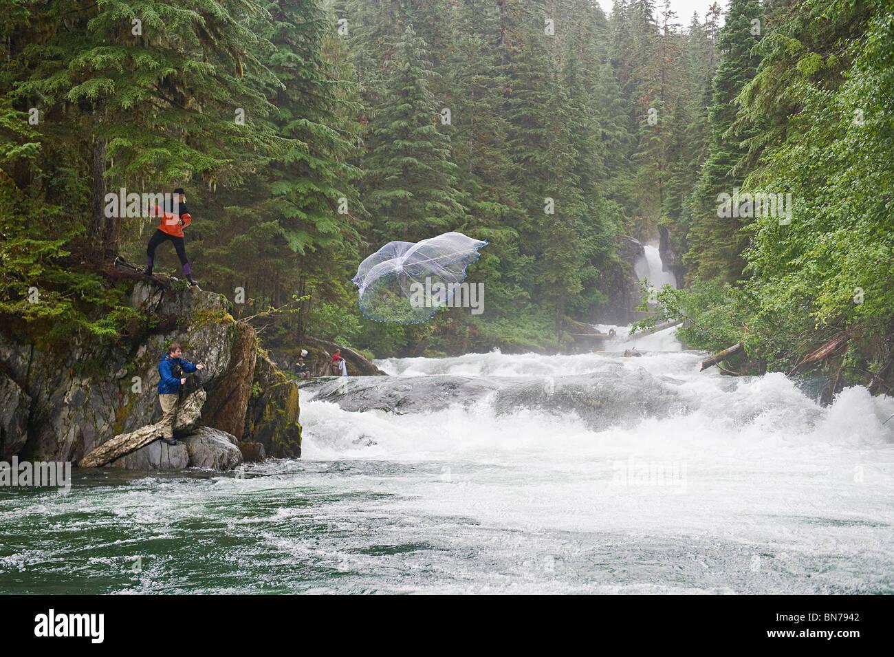 Two fishermen use a cast net to fish for Sockeye salmon in Sweetheart Creek in Alaska - Stock Image