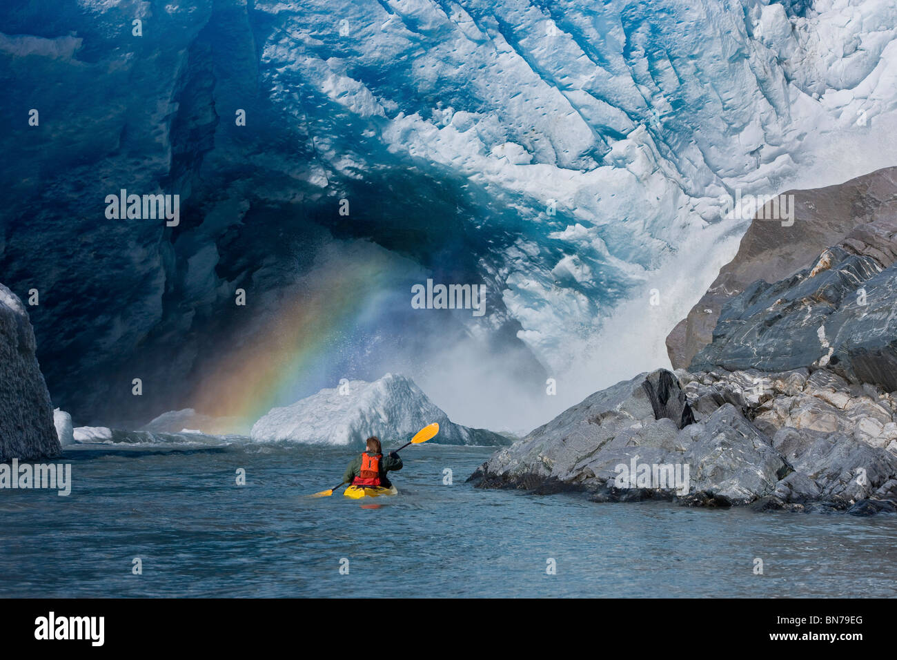 A kayaker explores a melt stream gushing from beneath Mendenhall Glacier, Mendenhall Lake, Tongass National Forest, - Stock Image