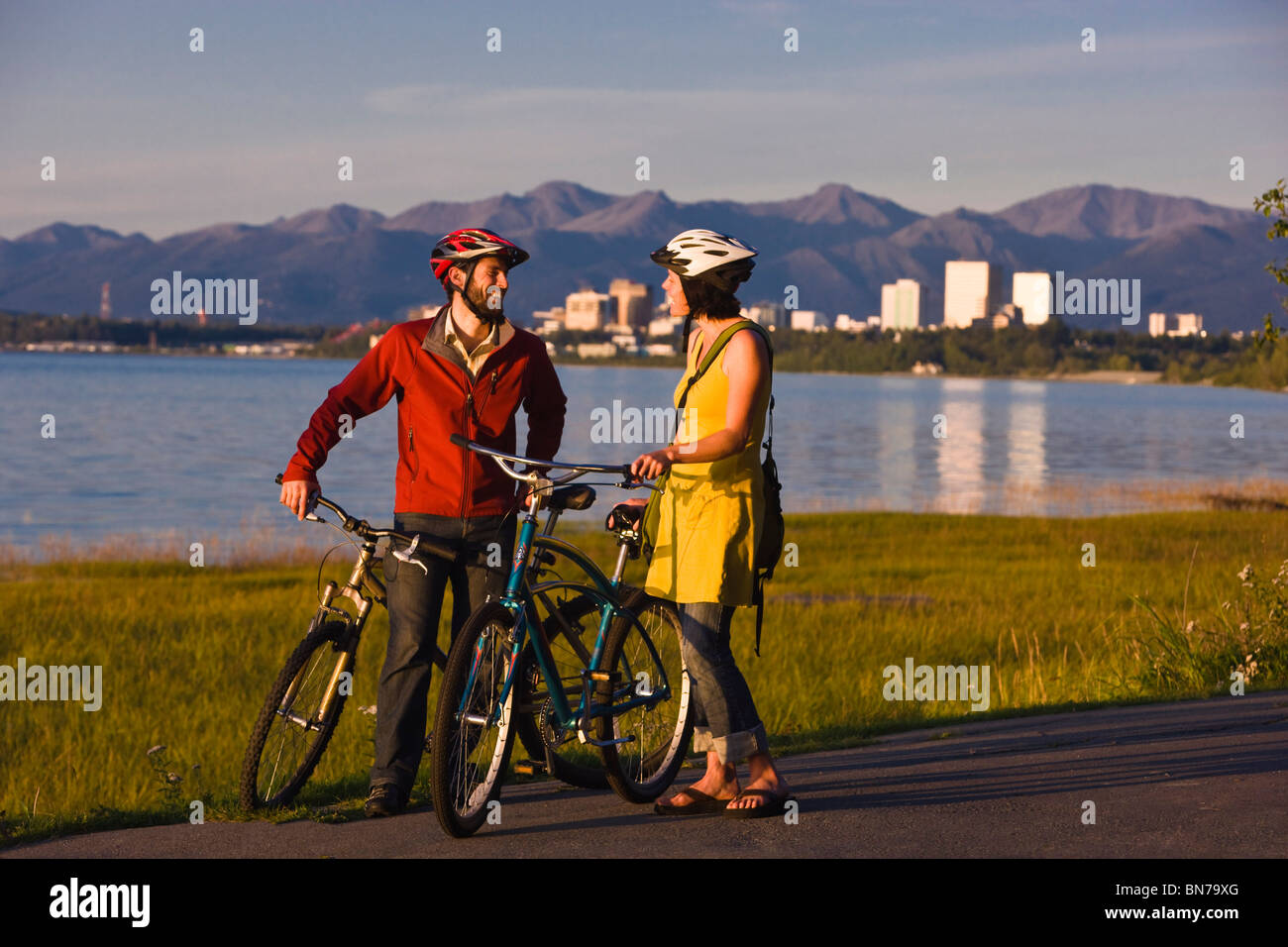 Bicyclists rest and take self-portraits along the Tony Knowles Coastal Trail with Anchorage in the background, Alaska - Stock Image