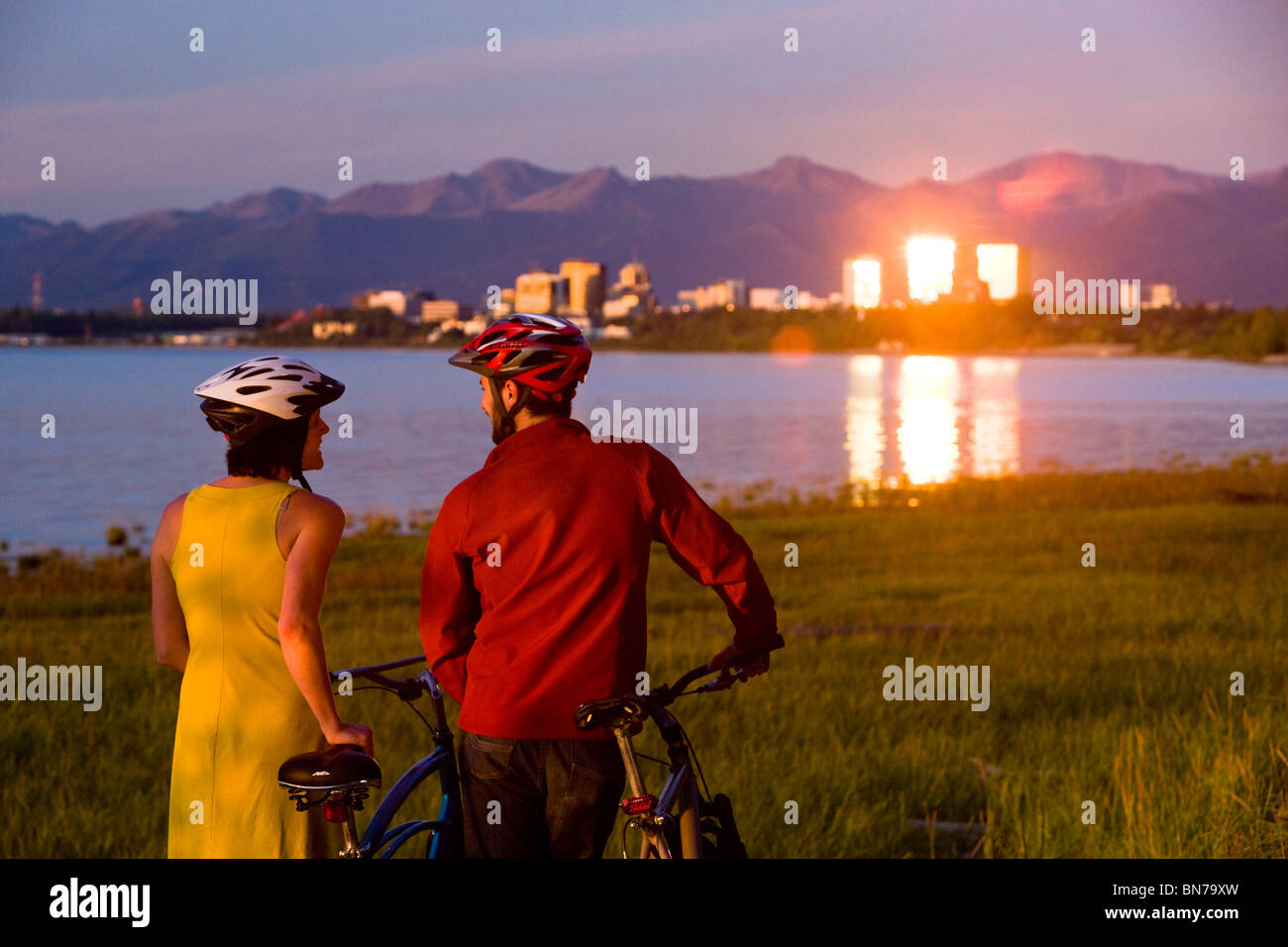 Bicyclists rests and and enjoys the sunset along the Tony Knowles Coastal Trail with the Anchorage in the background, - Stock Image
