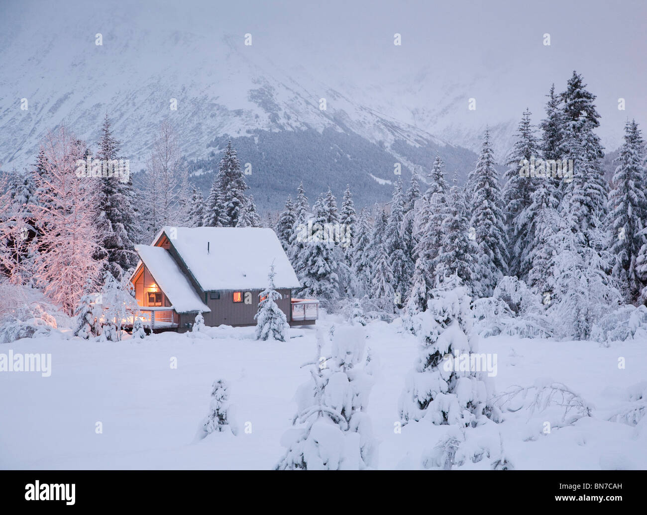 Snowcovered home in a wintry meadow at dawn with inside lights on, Girdwood, Alaska - Stock Image