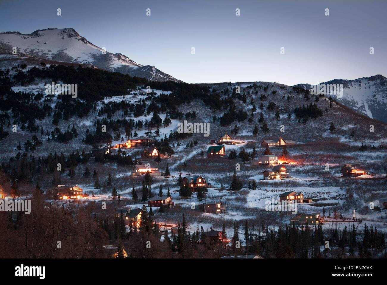 Winter view of hillside homes with lit interiors at dusk with Chugach Mountains in the background, Anchorage, Alaska Stock Photo