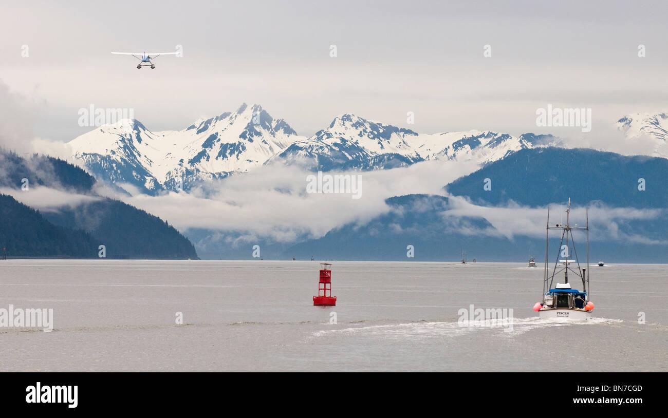 A floatplane flies down Gastineau Channel as gillnetters head to the fishing grounds in Taku Inlet near Juneau, - Stock Image