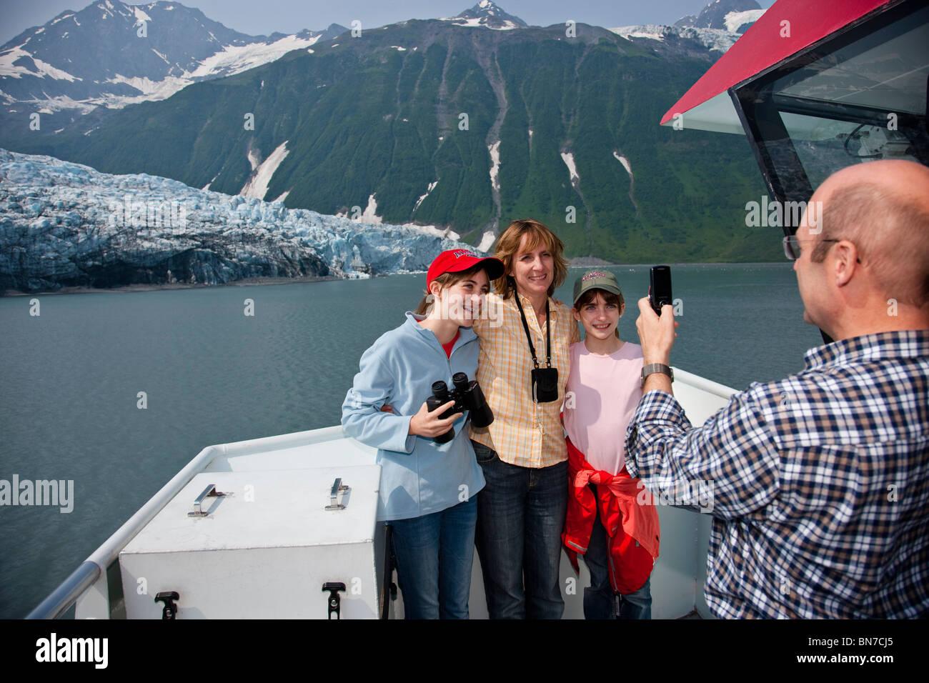 Father taking photos of his family with a cell phone while sightseeeing in Prince Wiliam Sound, Harriman Glacier, - Stock Image