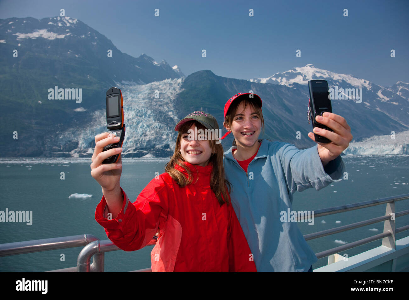 Teenage sisters taking photos of themselves with a cell phone near Harriman Glacier, Prince William Sound, Alaska - Stock Image