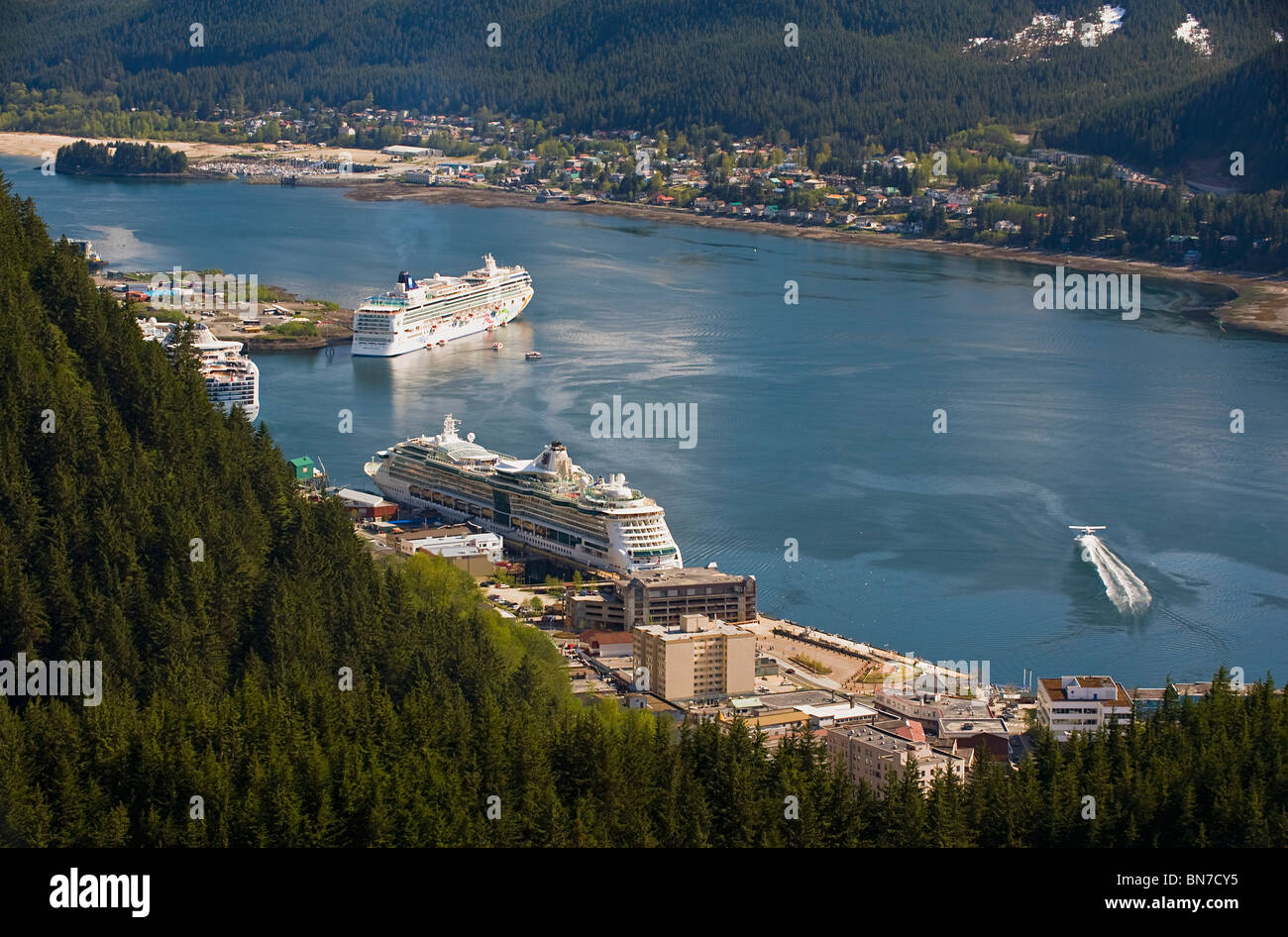 A floatplane takes off in Gastineau Channel with a view of three cruise ships docked in downtown Juneau, Alaska - Stock Image